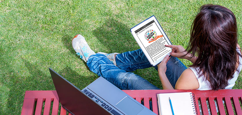 Girl studying on grass looks at microlearning modules on ipad